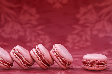 Row of red strawberry macarons with copy space.