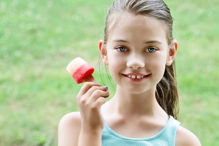 paletas de hielo: Ni�a comiendo un saludable sand�a helados caseros hechos con sand�as y limas.