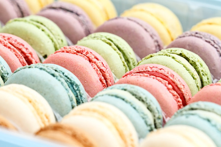 Box of fresh colorful macarons. Extreme shallow depth of field with selective focus on center macarons.