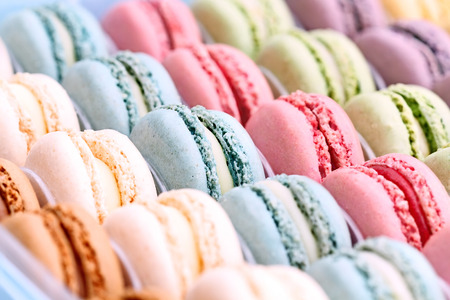 french cuisine: Box of fresh colorful macarons. Extreme shallow depth of field with selective focus on center blue macaron.