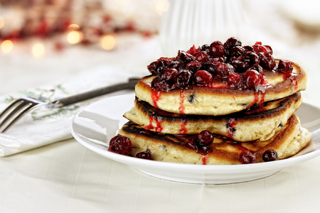 Cranberry sauce made with maple syrup, butter and fresh cranberries over delicious golden pancakes for Christmas morning. Extreme shallow depth of field with selective on pancakes. Standard-Bild
