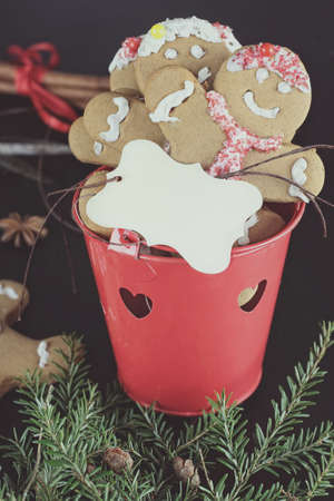 boughs: Gingerbread cookies and name tag with pine boughs, cones, cinnamon, amd anise over a dark background.