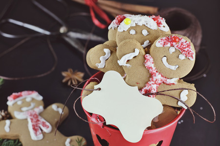 no person: Gingerbread cookies and name tag with pine boughs, cones, cinnamon, amd anise over a dark background. Extreme shallow depth of field. Vintage tones. Stock Photo