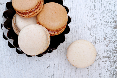 Above shot of chocolate and vanilla macarons over a rustic wooden background. Shallow depth of field.