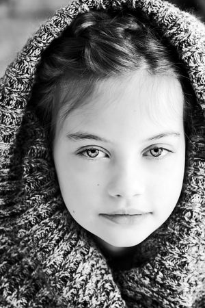 Black and white studio shot of a beautiful young girl in a hooded sweater with shallow depth of field.