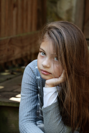 Jong meisje op zoek rechtstreeks in de camera met lange wapperende haren. Extreme ondiepe scherptediepte.