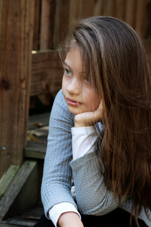 tween: Young girl sitting on porch steps with long hair falling loosely around her face. Extreme shallow depth of field. Stock Photo