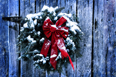 Rustic Christmas wreath on old weathered barn in a snow storm. Stockfoto