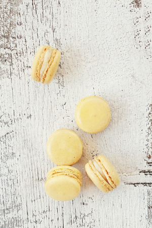 Vanilla macarons over a rustic wooden background with a retro tone. Stock Photo