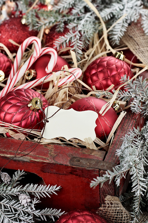 over packed: Christmas tag over glass Christmas ornaments and candy canes packed in an old antique wooden box with snow covered pine boughs surrounding them. Extreme shallow depth of field with selective focus on tag. Stock Photo