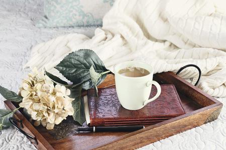 Eine heiße entspannende Tasse Kaffee mit einem Buch und Blumen in einem Serviertablett auf einem bequemen Bett mit Decke sitzt. Extrem flache Schärfentiefe.