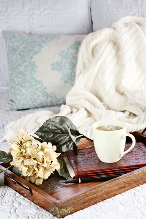 throw cushion: A hot relaxing cup of coffee with a book and flowers in a serving tray sitting on a comfortable bed with blanket. Extreme shallow depth of field. Stock Photo