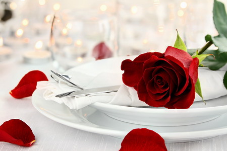 setting: Romantic candlelite table setting with long stem red rose. Shallow depth of field with selective focus on rose.