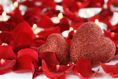 Valentines Day hearts surrounded by rose petals and lite candles against a white background. Room for copy space with extreme shallow depth of field. Stock Photo