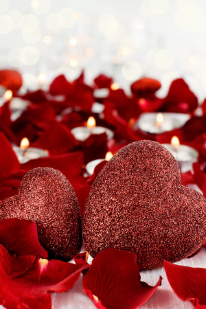 room for copy: Valentines Day hearts surrounded by rose petals and lite candles against a white background. Room for copy space with extreme shallow depth of field. Stock Photo
