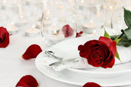 Romantic table setting with long stem red rose and candles burning in the background. Shallow depth of field with selective focus on rose.