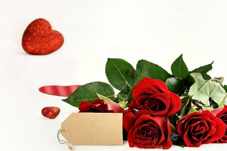 room for copy: Red roses with an empty label and glitter hearts in the background. Room for copy space with extreme shallow depth of field.