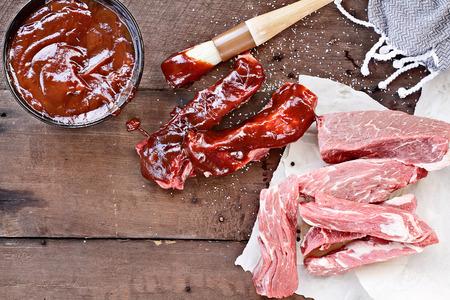 costillas país con salsa de barbacoa y pincel de cocina sobre una mesa rústica.