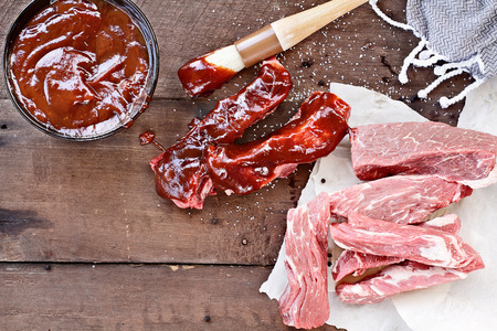 raw beef: Country ribs with barbecue sauce and basting brush over a rustic table.