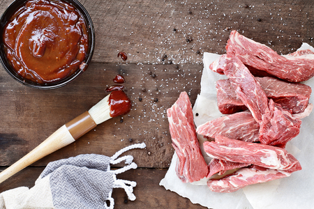 Country ribs with barbecue sauce and basting brush over a rustic table.
