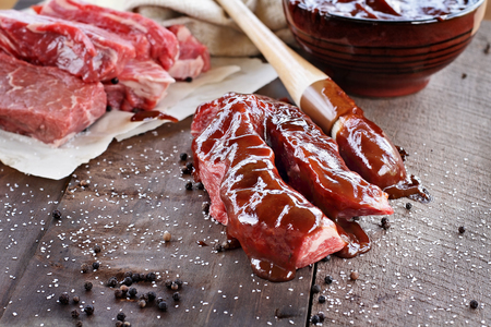 photography background: Country ribs with barbecue sauce and basting brush over a rustic table.