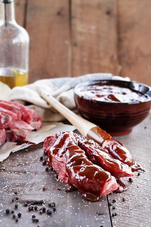 rib: costillas país con salsa de barbacoa y pincel de cocina sobre una mesa rústica. Foto de archivo
