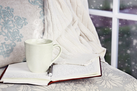A hot relaxing cup of coffee or cocoa with an open book sitting on a comfortable chair with blanket. Extreme shallow depth of field.