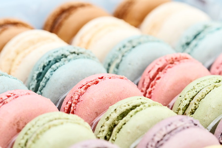 Box of fresh pastel colored macarons. Extreme shallow depth of field with selective focus on center red macaron.