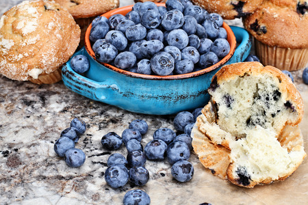 baked goods: Bowl of fresh blueberries and delicious homemade blueberry muffins.