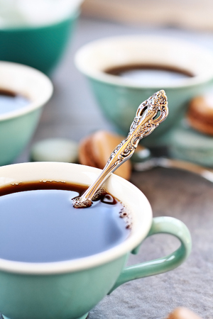 food photography: Abstract of a closeup of a vintage teaspoon in a cup of coffee with extreme shallow depth of field with selective focus on spoon.