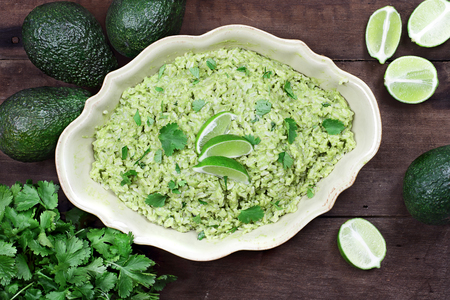 overhead shot: Overhead view of Avocado Lime Cilantro Rice with fresh ingredients against a rustic wooden background.
