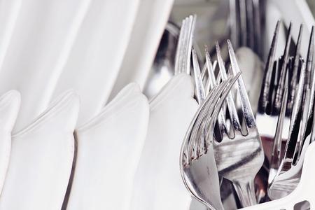 Résumé des fourchettes propres et des plats à l'intérieur d'une machine à laver la vaisselle. Extreme faible profondeur de champ avec un accent sélectif sur la fourche. Banque d'images - 54929840