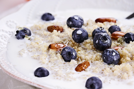 Cooked Quinoa with blueberries, almonds and honey. Selective focus with extreme shallow depth of field. Banque d'images