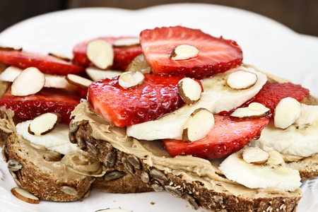Healthy wholefoods breakfast of whole grain toast, peanut butter, bananas, fresh strawberries, almonds, and honey.