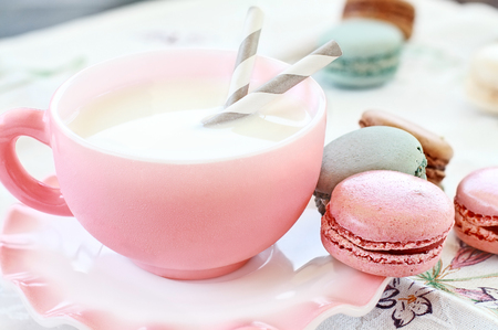 Colorful macarons with cup of milk. Extreme shallow depth of field with selective focus on pink macaron. Stock Photo
