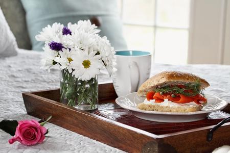 стиль жизни: Лосось на Ciabatta завтрак в и цветы служили в постели День матери. Фото со стока