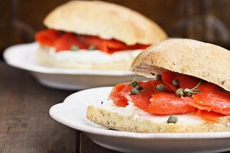 salmon ahumado: Salmón, queso crema y alcaparras en pan ciabatta. Extrema profundidad de campo con enfoque selectivo. Foto de archivo