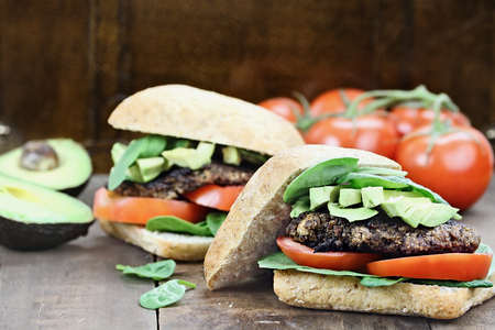 avacado: Vegetarian hamburger made from ground mushrooms with avocados, tomatoes and spinach. Dairy and meat free. Extreme shallow depth of field with selective focus.