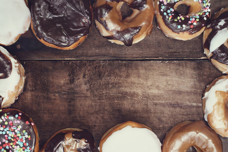 filled out: Variety of donuts over a rustic background shot from overhead with copyspace.