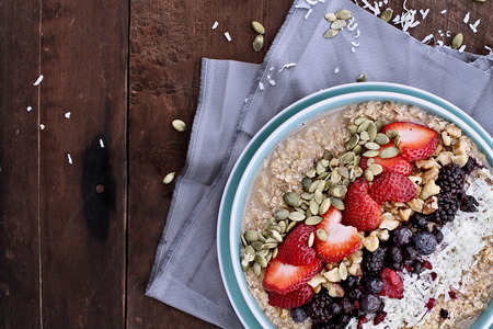 Hot breakfast of healthy oatmeal with shredded coconut, blackberries, blueberries, walnuts, heart shaped strawberries and pumpkin seeds over a rustic background. Image shot from overhead.