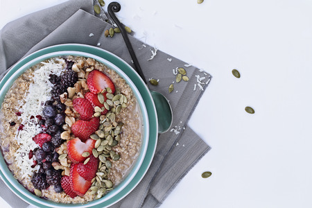 shredded coconut: Hot breakfast of healthy oatmeal with shredded coconut, blackberries, blueberries, walnuts, heart shaped strawberries and pumpkin seeds over a white background. Image shot from overhead.