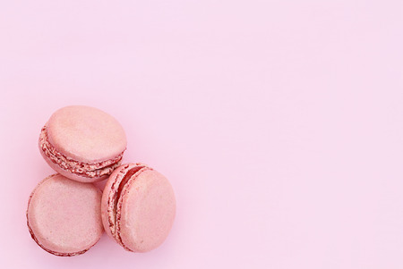 Three pink macarons over a pink background with copy space available.