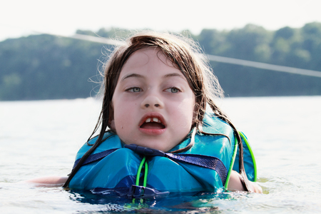 life jacket: Frightened little girl in a lake wearing a life jacket. Stock Photo