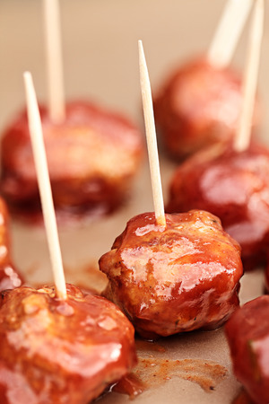 toothpick: Delicious turkey meatballs in a rich tomato sauce. Extreme shallow depth of field with selective focus on center of image.