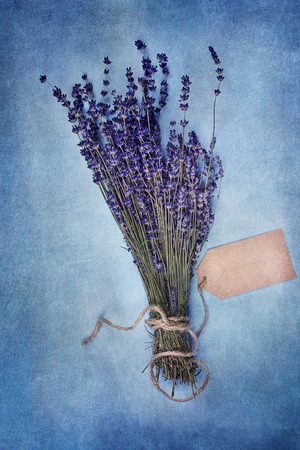 Overhead view of a bundle of dried lavender flowers with blank tag over a textured background.