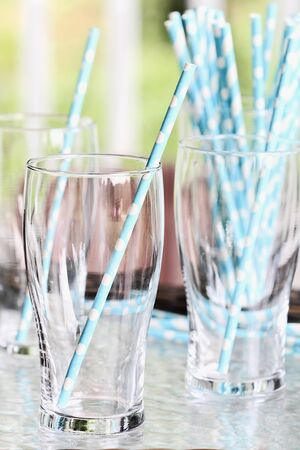 foreground focus: Clean empty drinking glasses with party straws on an outdoor table. Extreme shallow depth of field with selective focus on foreground.