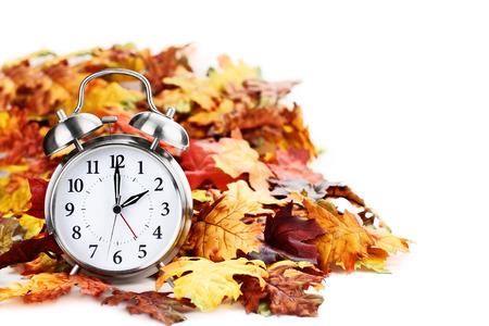reloj de alarma en el colorido del otoño deja aislado contra un fondo blanco con la sombra de la luz y la profundidad de campo. El horario de verano concepto de tiempo.