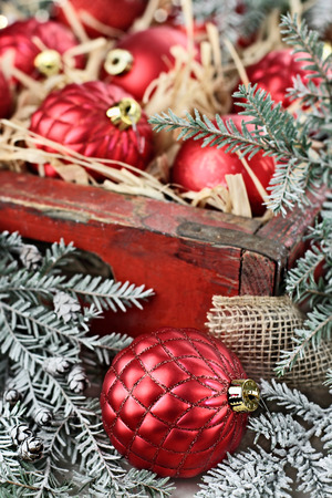 boughs: Glass Christmas ornaments packed in an old antique wooden box with snow covered pine boughs surrounding them. Extreme shallow depth of field with selective focus on bauble in front. Stock Photo