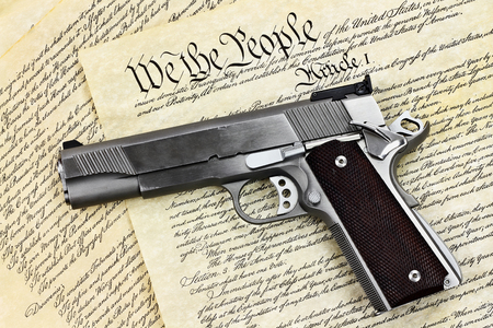 Handgun lying over a copy of the United States constitution with the words We the People visible.