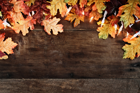 Rustic fall background of autumn leaves and decorative lights over a rustic background of barn wood. Image shot from overhead.